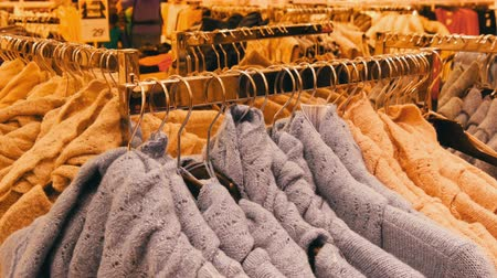 sem camisa : Large number of new warm stylish sweaters of different colors hanging on hangers in the clothing store shopping center or mall. Fashionable collection of warm clothes. Stock Footage