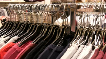 сантиметр : A large number of womens clothing of different colors hangs on hangers and lies on the shelves in a clothing store of shopping center or mall. The problem of consumerism Стоковые видеозаписи