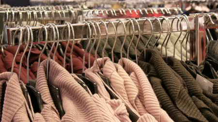 tüketmek : Large number of new warm stylish sweaters of different colors hanging on hangers in the clothing store shopping center or mall. Fashionable collection of warm clothes. Stok Video