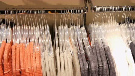 lavanderia : Various multi-colored womens clothing hanging on hangers in a clothing store in mall or shopping center Stock Footage