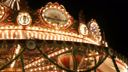 recreational park : Nuremberg, Germany - December 1, 2018: Fascinating flashing lights dark night sky illumination of vintage merry go round fair carousel ferris wheel in christmas market