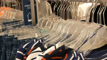 lavanderia : Various multi-colored womens clothing and jeans hanging on hangers in a clothing store in mall or shopping center Stock Footage
