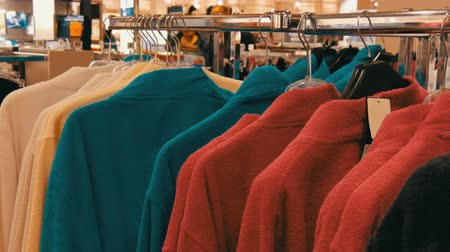 пуховое одеяло : Number of different multicolored bathrobes on the hanger in the store of the shopping center Стоковые видеозаписи