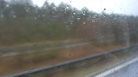 运输 : Close-up shot of rain drops and streaks on the window od moving bus by city street in deep autumn 影像素材