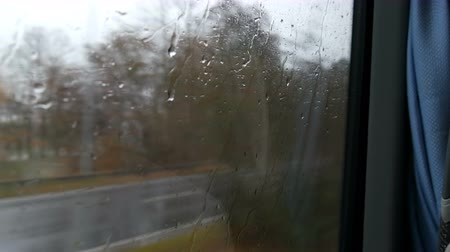 nuremberg : Close-up shot of rain drops and streaks on the window od moving bus by city street in deep autumn Stock Footage