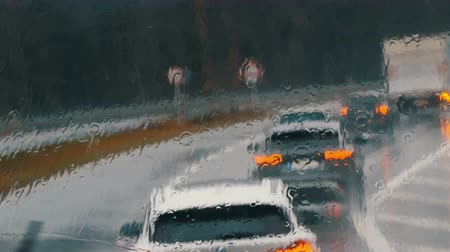 nuremberg : View of the traffic jam on the highway during rain. Cars go in a row. Shot of rain drops and streaks on the window od moving bus in a deep autumn Stock Footage