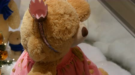 yumuşaklık : Princess toy brown teddy bear in a dress and crown spinning around in a Christmas-decorated shopping center Stok Video