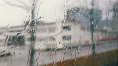 driveway : Close-up shot of rain drops and streaks on the window od moving bus by city street in deep autumn Stock Footage