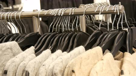 ramínko : Fashionable collection of warm clothes. Large number of new warm stylish sweaters hanging on hangers in the clothing store shopping center or mall.