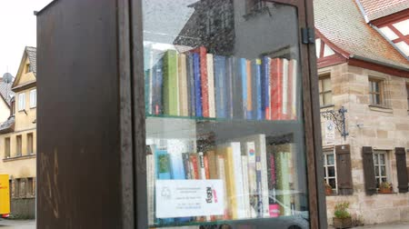 işlenmiş : Furth, Germany - December 3, 2018: The world famous bookcrossing movement in Germany. Special shelves with books written in German, which stands on the street.