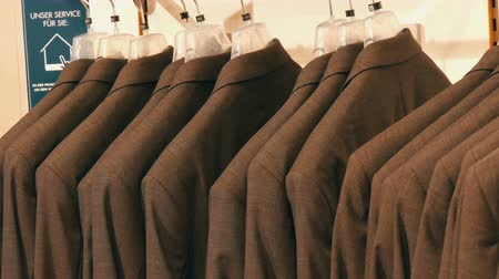casual wear businessman : Number of identical-colored mens suits hanging on a hanger in a clothing store in a mall Stock Footage