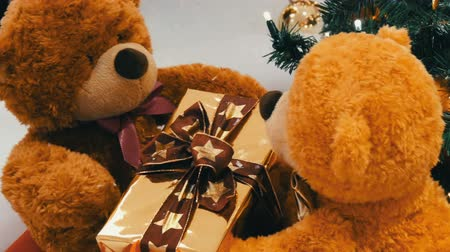peluş : Funny brown moving teddy bears that hold a box with a gift in their paws. Christmas decorations in mall Stok Video