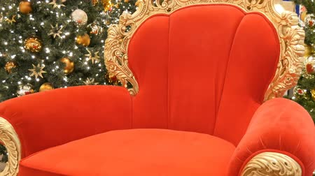 fotel : Red chair of Santa Claus or St. Nicholas near christmas tree at the mall. Christmas decor shopping center