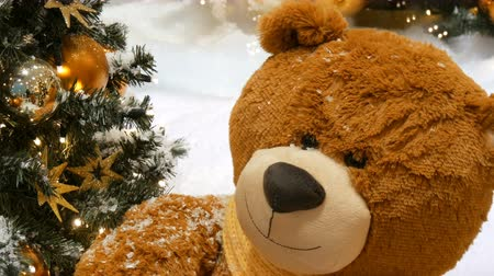 festoon : Toy brown bear as a decor near beautifully dressed Christmas tree in a mall or shopping center