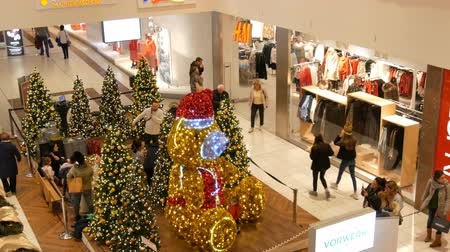festoon : Nuremberg, Germany - December 1, 2018: decorated Christmas trees with large gold and silver balls, stars, garlands and artificial snow and big bear are in shopping center with strolling shoppers