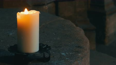 nuremberg : Large wax white candle burns and stands in an old candlestick in an old medieval church in Germany.