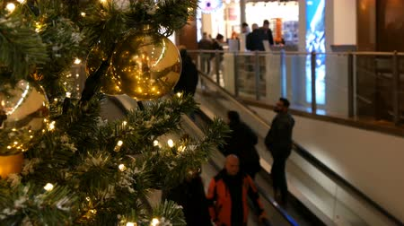 festoon : Nuremberg, Germany - December 1, 2018: Beautifully decorated Christmas tree on the background of two escalators in mall that go up and down on which buyers stand