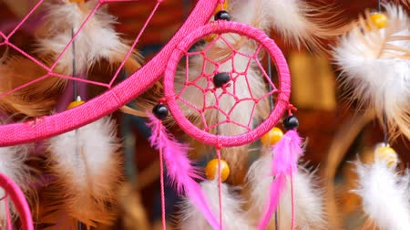 breezy : The pink feathers of a dreamcatcher who sway in wind