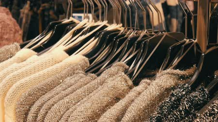tüketmek : Row of beautiful warm womens fluffy sweaters of gray, black and white are hanging on black hangers in the store of the shopping center or mall. Fashionable collection of warm clothes. Stok Video