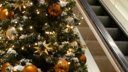 festoon : Beautifully decorated Christmas tree with large gold and silver balls, stars, garlands and artificial snow is standing in the shopping center or mall, people are passing by on the escalator