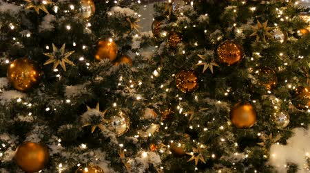 boncuk : Beautifully decorated Christmas tree with large gold and silver balls, stars, garlands and artificial snow is standing in the shopping center close up view Stok Video