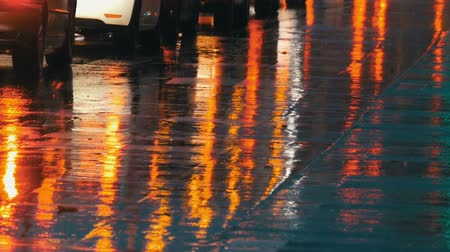 pocsolya : Cars in traffic, headlights in rain on asphalt, view below. Rain hits the puddles at night. Reflection of cars lights Stock mozgókép
