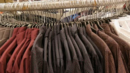 vállfa : Row of various fashionable mens shirts on a huge hanger in the mens clothing store in the shopping center.