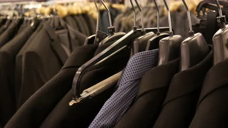 vállfa : A number of different fashionable mens black jackets and shirts on the hanger in the mens clothing store in the shopping center. Stock mozgókép