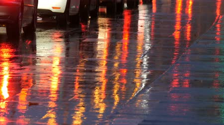 poz : Cars in traffic, headlights in rain on asphalt, view below. Rain hits the puddles at night. Reflection of cars lights Stok Video