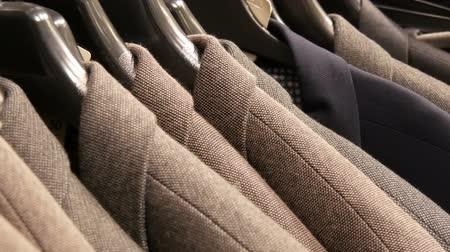 casual wear businessman : Stylish brown wool jackets hang on hangers in the mall. Stock Footage