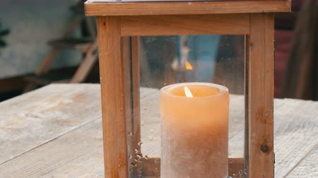 plamen : Large wax candle in a stylish wooden candlestick on the table of a street cafe.