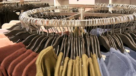 casual wear businessman : On big round hanger there are various stylish knitted multicolored sweaters hanging on fashion black hangers in a clothing store in mall or shopping center, close up view