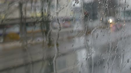 busz : Close-up shot of rain drops and streaks on the window od moving bus by city street in deep autumn Stock mozgókép