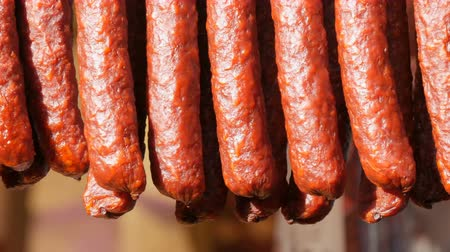 przekąski : A row of smoked sausages are hanging on the showcase of a butcher shop