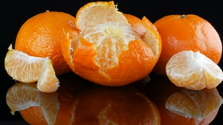 mandarynka : Ripe orange tangerines on a mirror surface on a black background.