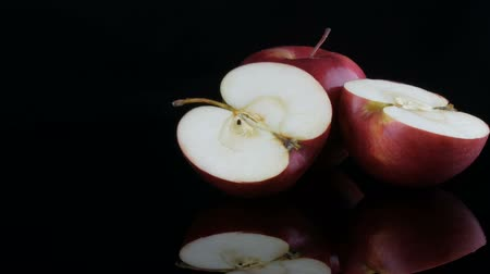 Beautiful ripe juicy red apples on the mirror surface and black background. Fruit, healthy food, diet.