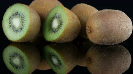 kivi : Stylish view of ripe sliced and whole kiwi fruit rotated on a mirror surface on black background in the studio Stok Video