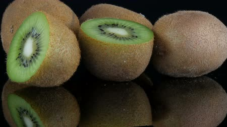 Stylish view of ripe sliced and whole kiwi fruit rotated on a mirror surface on black background in the studio Wideo