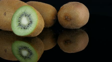 kivi : Female hands take ripe cut fruit next to whole kiwi on the mirror surface on a black background in studio Stok Video