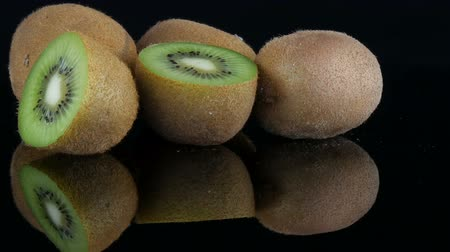 Stylish view of ripe sliced and whole kiwi fruit on a mirror surface on black background in the studio Stock Footage