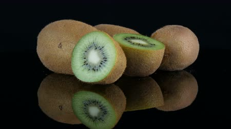 Stylish view of ripe sliced and whole kiwi fruit rotated on a mirror surface on black background in the studio Vídeos