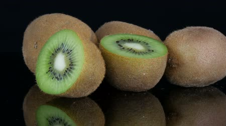 Stylish view of ripe sliced and whole kiwi fruit rotated on a mirror surface on black background in the studio Stock Footage