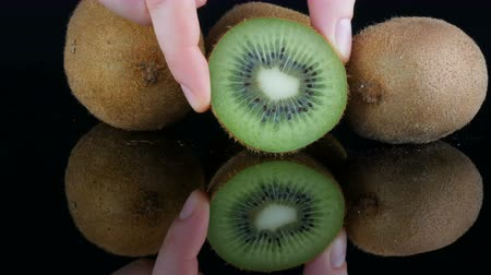 Female hands put ripe cut fruit next to whole kiwi on the mirror surface on a black background in studio Vídeos