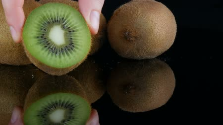 Female hands put ripe cut fruit next to whole kiwi on the mirror surface on a black background in studio Stock Footage