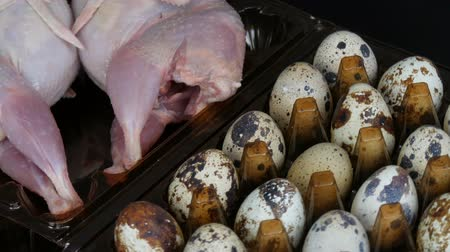Fresh meat of quail in a plastic brown tray next to the quail eggs on a black background.