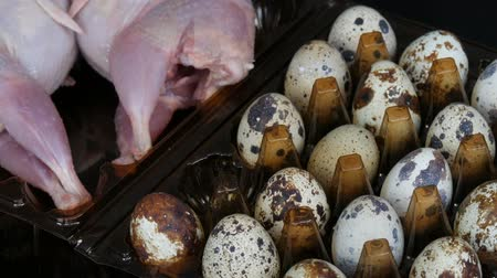 fürj : Fresh meat of quail in a plastic brown tray next to the quail eggs on a black background. Female hands take eggs from the tray.