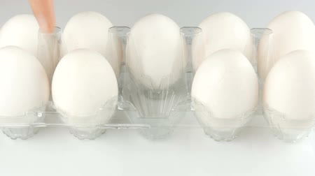 Large white chicken eggs in a transparent plastic tray on a white background. Female hands take eggs from the tray.