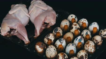 fürj : Fresh meat of quail in a plastic brown tray next to the quail eggs on a black background.