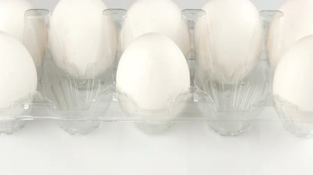 Large white chicken eggs in a transparent plastic tray on a white background. Female hands put the eggs in the tray Stock Footage