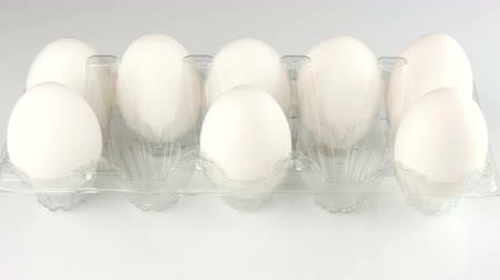 fehérjék : Large white chicken eggs in a transparent plastic tray on a white background. Female hands put the eggs in the tray Stock mozgókép